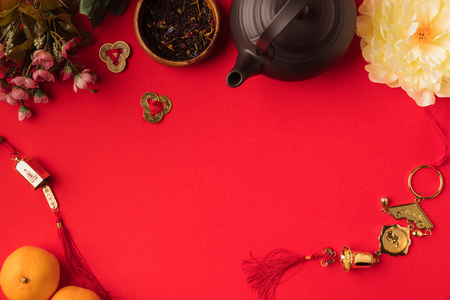top view of oriental decorations, tangerines, flowers and tea set isolated on red  版權商用圖片