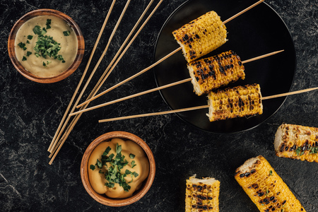 top view of grilled corn pierced with sticks and bowls of sauce