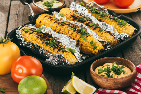 grilled corn covered in foil on frying pan with tomatoes and limes Reklamní fotografie