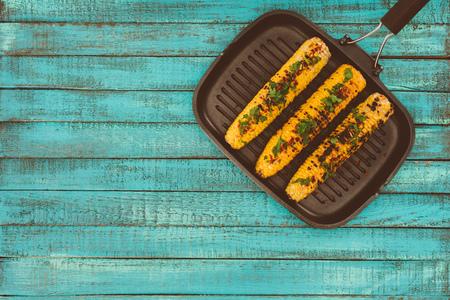 bovenaanzicht van geroosterde maïs op grillpan en op blauwe houten tafel Stockfoto