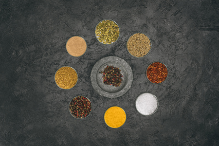 Top view of round of glass bowls with different spices on a gray tabletop