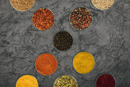 Top view of different spices in glass bowls on a concrete surface Фото со стока