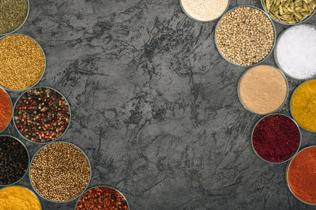 Top view of spices in bowls on a gray tabletop