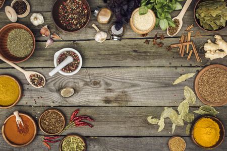 Top view of different spices and herbs on a gray wooden table