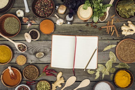 Top view of notebook for recipes with spices on a table Imagens