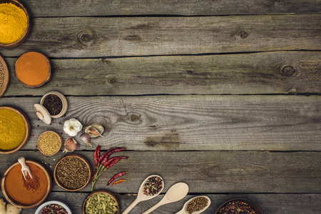 Top view of different spices in bowls and spoons on a wooden tabletop