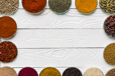 Top view of different spices in glass bowls on a white wooden table Stock Photo
