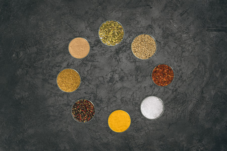 Top view of round of glass bowls with different spices