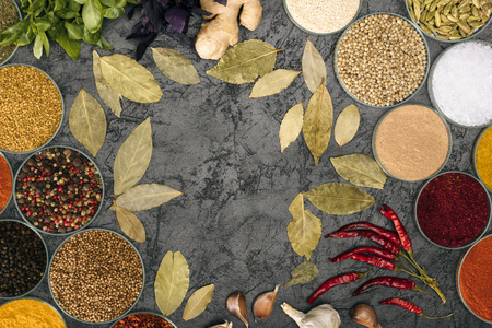 Top view of spices in bowls and scattered bay leaves on gray surface