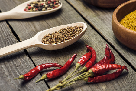 Chili peppers and spoons with spices on a wooden table