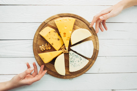 top view of female hands, arranged types of cheese and hazelnuts on wooden cutting board