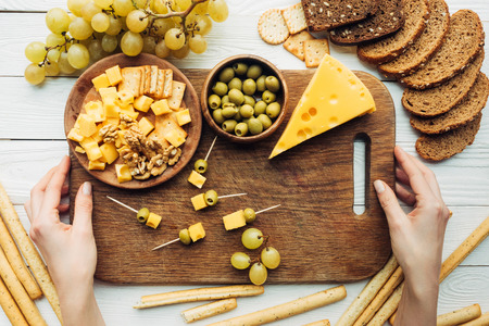 cropped shot of female hands holding wooden cutting board with olives, cheese and canapes Banco de Imagens