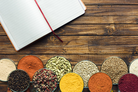 Top view of notebook for recipes and spices on a wooden tabletop