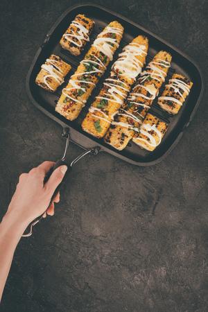 bovenaanzicht van de grillpan van de vrouwenholding met graan