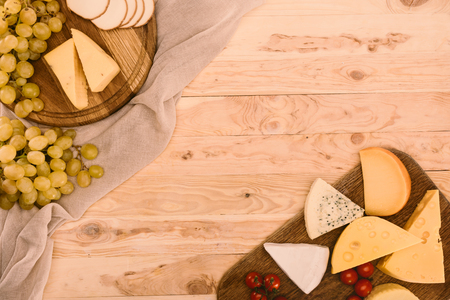 top view of various types of cheese on cutting boards, grapes and cherry tomatoes on wooden surface