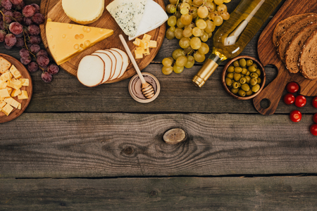 flat lay with various types of cheese on cutting board, honey, bread, olives and bottle of wine on wooden tabletop