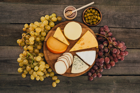 flat lay of assortment of cheese types on cutting board, grapes, honey and olives on wooden surface Stock Photo