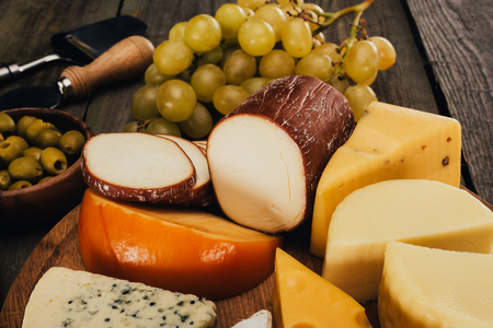 close up view of assortment of cheese on wooden cutting board and grapes
