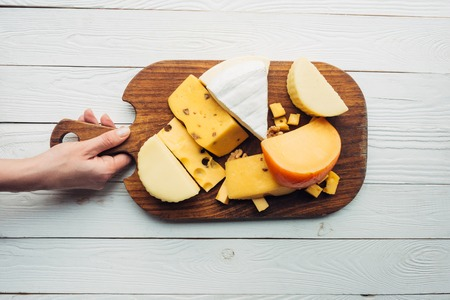 top view of female hand holding assorted cheese on wooden cutting board