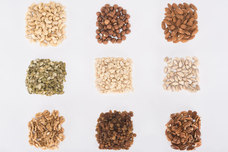 top view of heaps of various delicious healthy nuts isolated on white Stock Photo