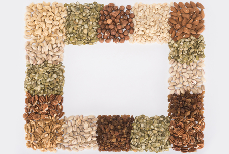 top view of frame made from assorted healthful nuts on white