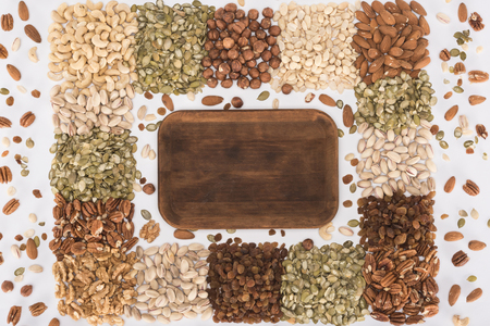 top view of healthy assorted nuts and empty wooden board on white  版權商用圖片
