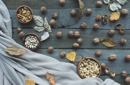 top view of assorted nuts in bowls, walnuts and dried autumn leaves on wooden table