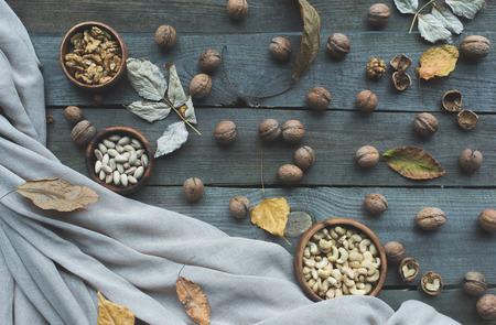 Vista dall'alto di dadi assortiti in ciotole, noci e foglie di autunno essiccate sul tavolo di legno Archivio Fotografico - 89983440