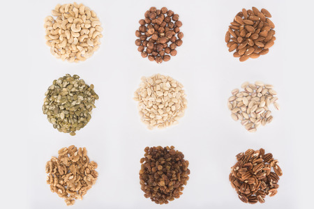 top view of heaps of assorted delicious healthy nuts isolated on white Stock Photo