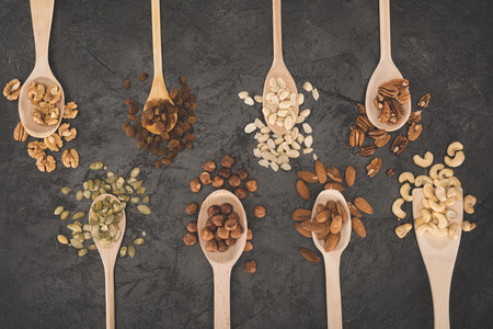 top view of assorted nuts in wooden spoons on black Stock fotó