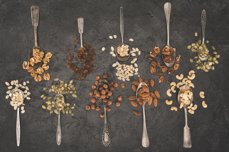 top view of various healthy dried nuts in spoons on black