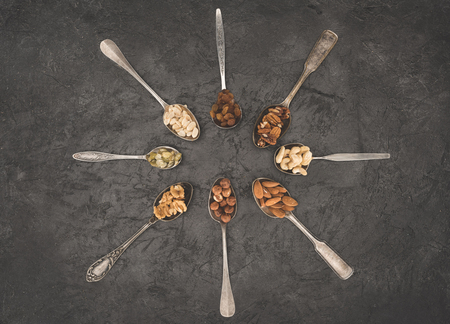 top view of various dried nuts in spoons on black   Stock Photo