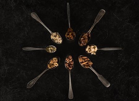 top view of assorted dried nuts in spoons on black   Zdjęcie Seryjne