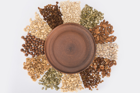 top view of healthful assorted nuts and empty round plate isolated on white