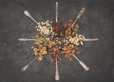 top view of various nuts in spoons on black   Stok Fotoğraf