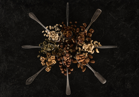 top view of assorted nuts in spoons on black