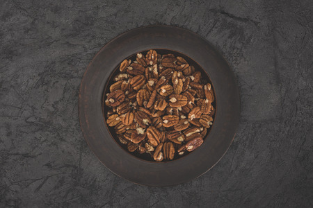 top view of delicious pecan nuts in bowl on black  Stock Photo