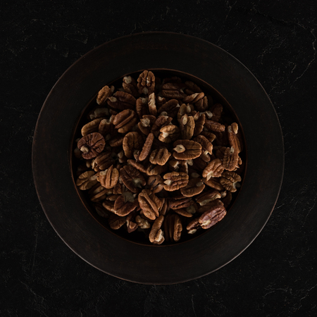 top view of delicious healthy pecan nuts in bowl on black