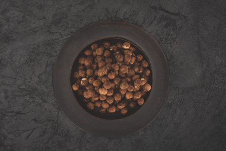 top view of healthy hazelnuts in plate on black