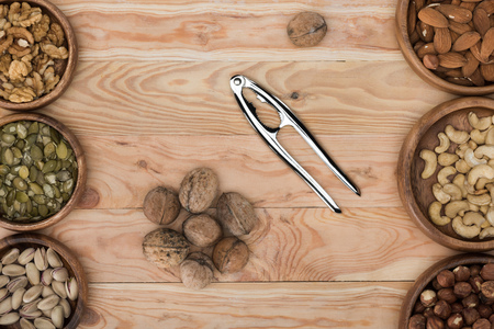 top view of various nuts in bowls, nutcracker and walnuts on wooden table