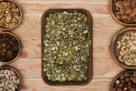 top view of pumpkin seeds, raisins and assorted nuts in bowls on wooden table