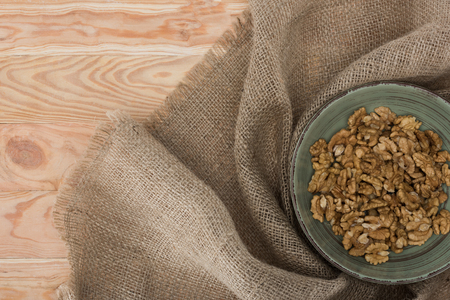top view of shelled walnuts in bowl and sackcloth on wooden table