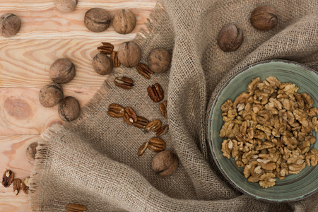 top view of shelled walnuts in bowl, sackcloth and whole nuts on wooden table