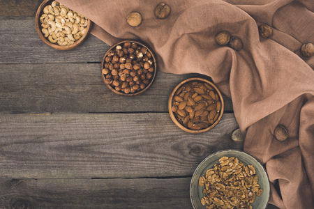 top view of assorted nuts in bowls and fabric on wooden table
