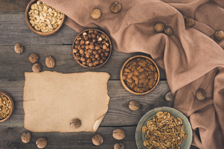 top view of various nuts in bowls and blank parchment on wooden table