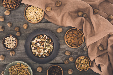 top view of various nuts in bowls and fabric on wooden table Stockfoto