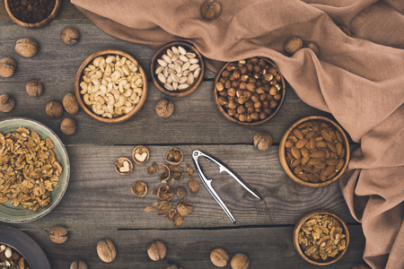 top view of various nuts in bowls, nutshells and nutcracker on wooden table  Stock Photo
