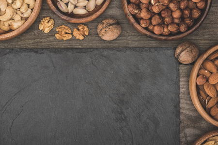 top view of nuts in bowls and blank slate board