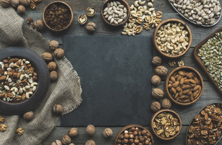 top view of assorted nuts in bowls and slate board on wooden table