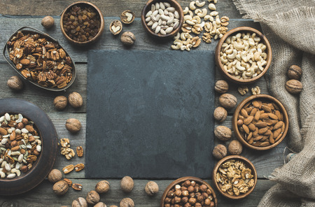 top view of various nuts in bowls, sackcloth and slate board on table